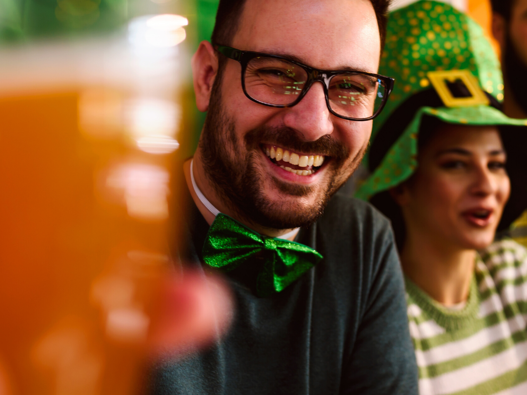 Couple celebrating St. Patrick's Day Man holding beer women with leprechaun's hat