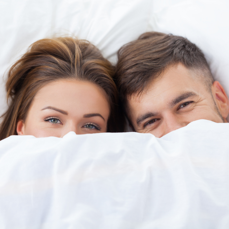 Couple Cozy & smiling under the white comforter