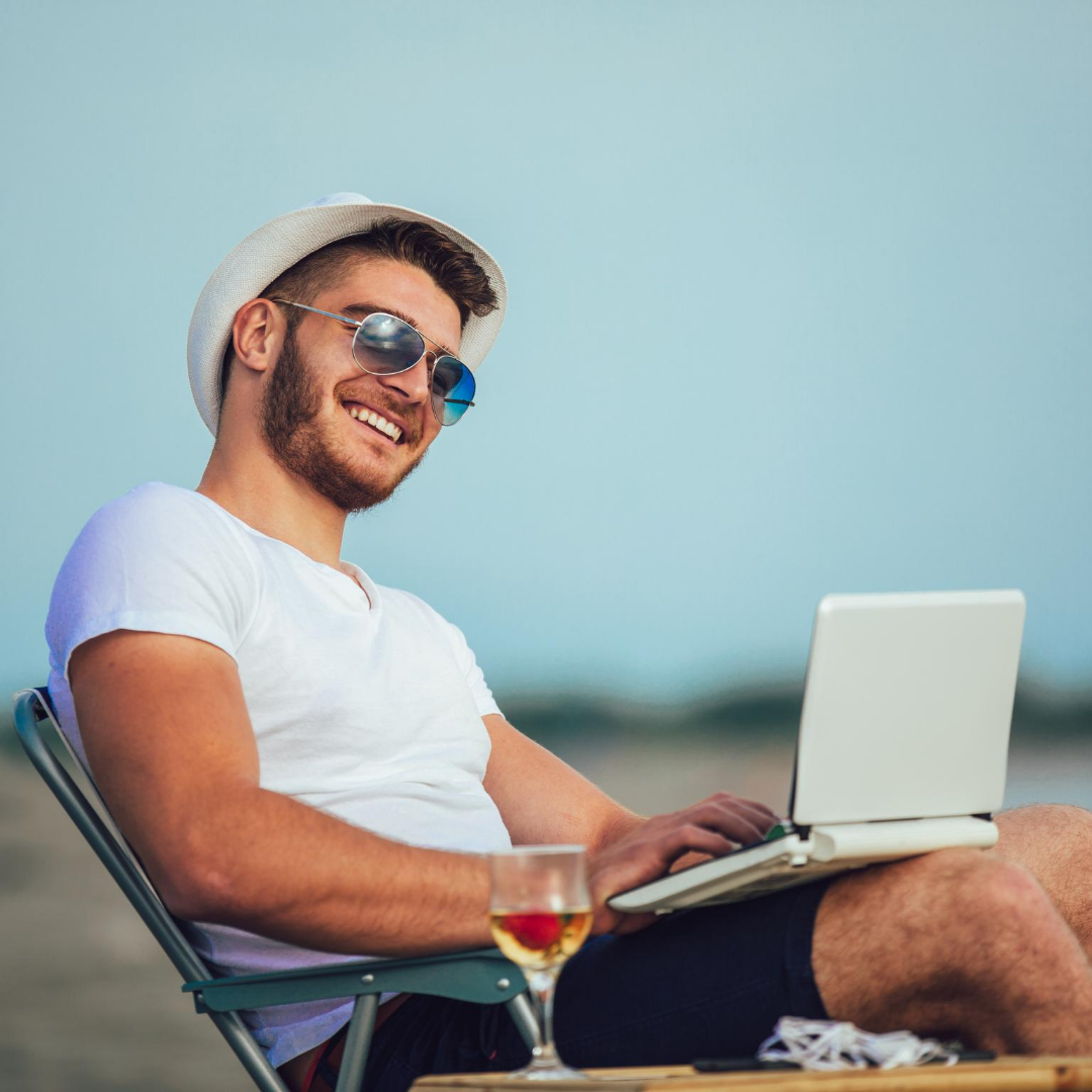 Young man sitting on beach chair in sunglasses and fedora smiling with laptop and a glass of wine