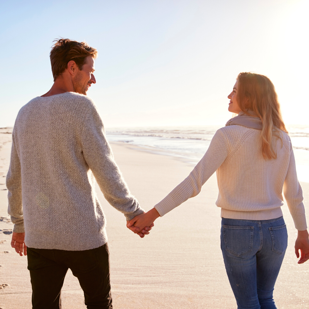 White Couple in Cozy Sweaters Holding Hands on the Beach
