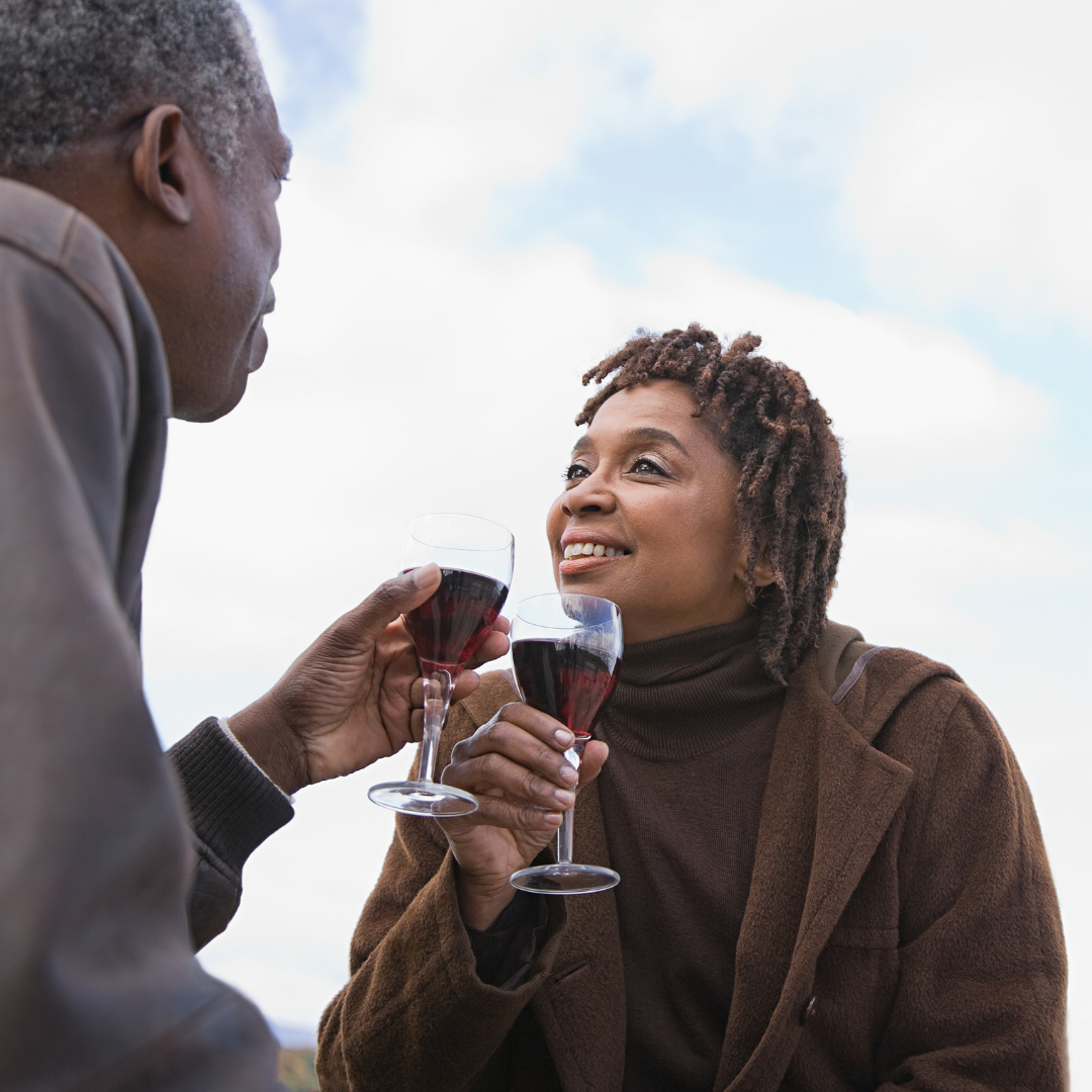 Black couple enjoying red wine by the beach