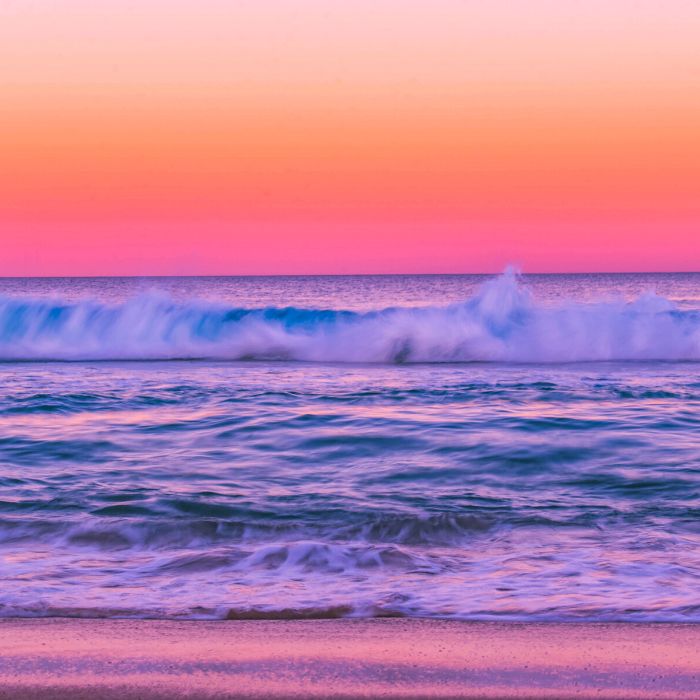 Incredible fall sunset with orange, deep pink, purple over the ocean waves