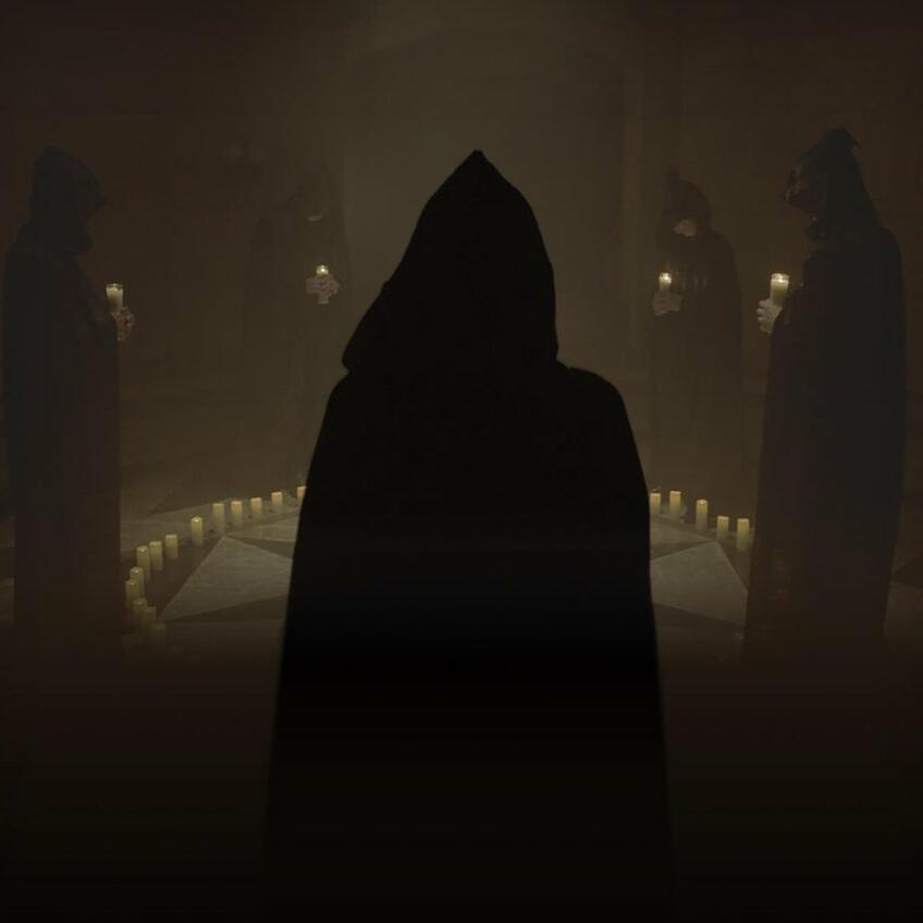 An image of a group of people wearing black cloaks and performing a ritual