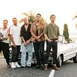 Image of the SIX60 Band standing in front of the car