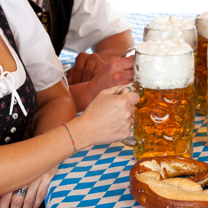 Oktoberfest lady with dirndl outfit and steins of beer and giant pretzel