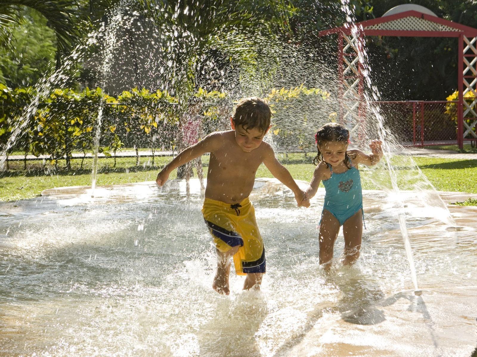 Two children having fun with water at Fiesta Resort