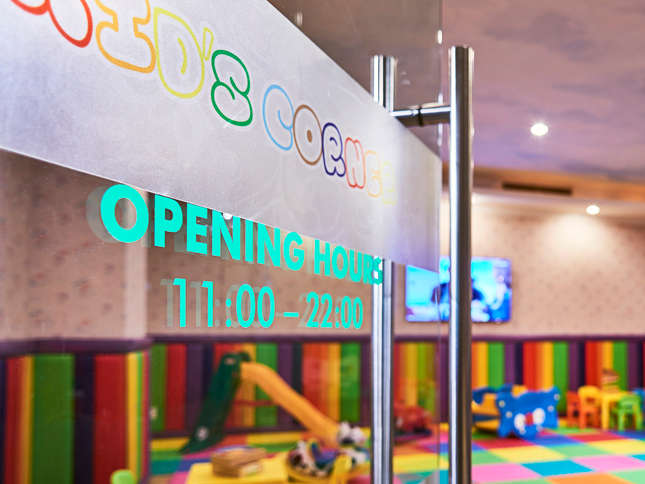 glass door entrance to hotel kids corner with colourful play area