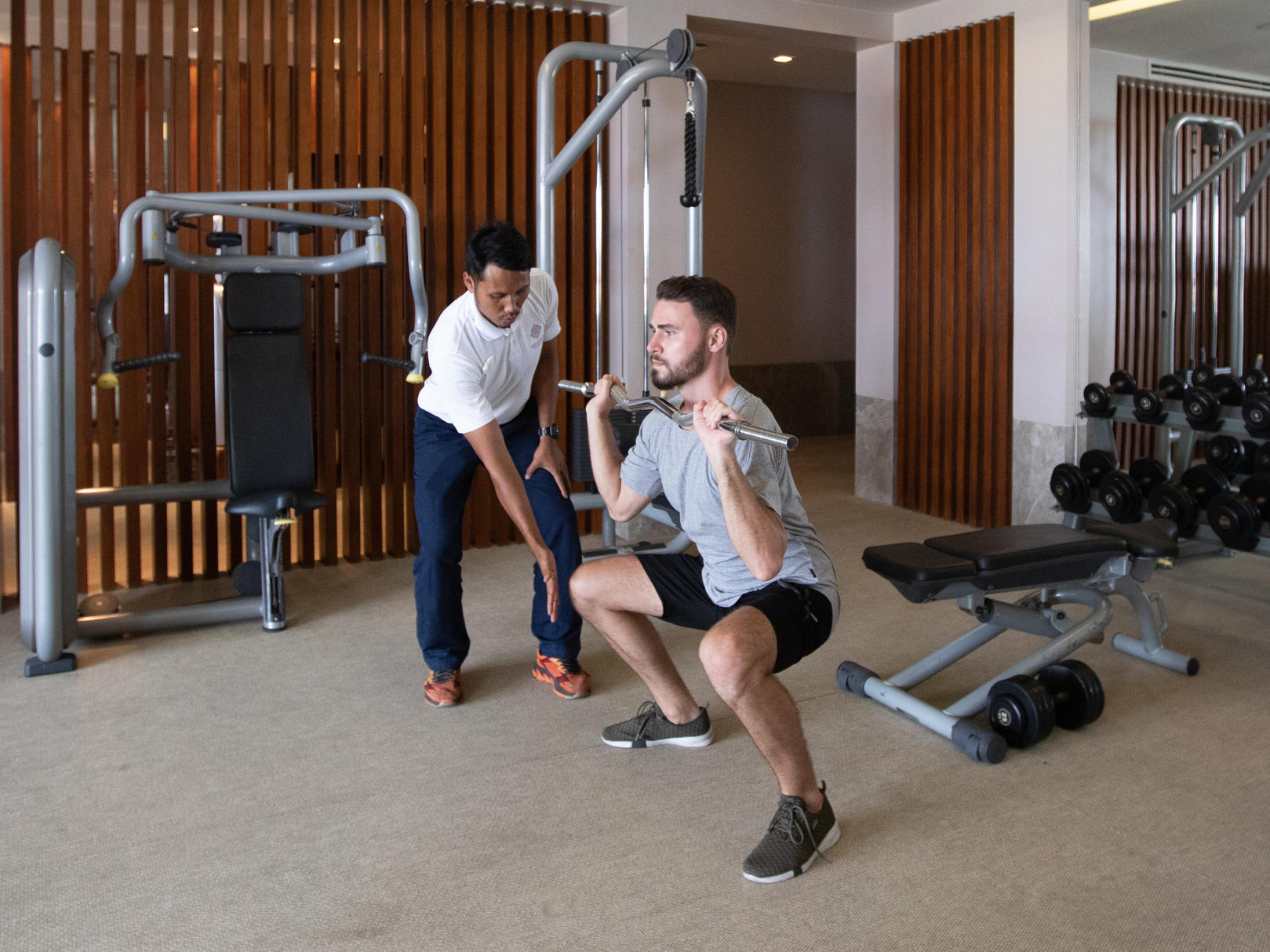 a male guest working out in the gym with a fitness instructor