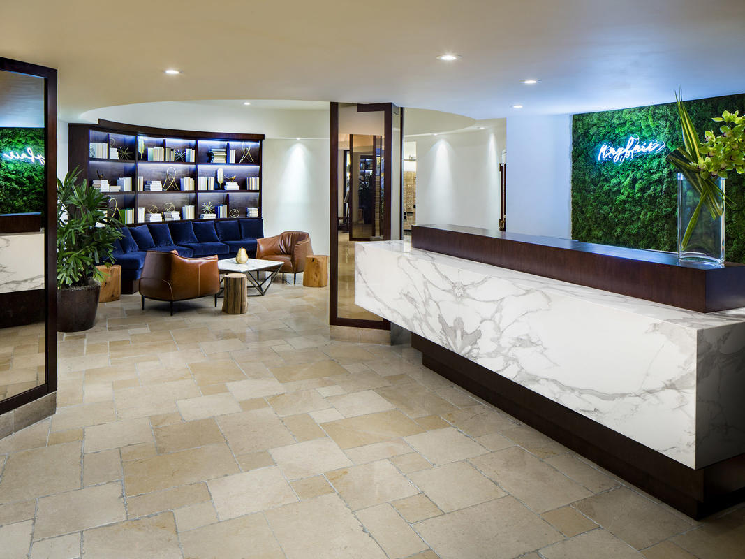 lobby with marble front deask and grass wall