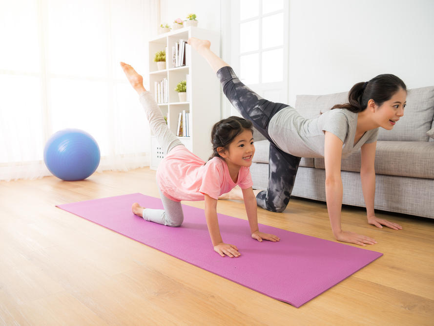 woman and little girl practicing yoga in living room