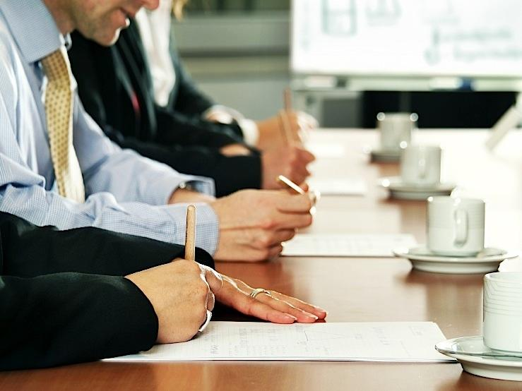 business people writing on paper at meeting
