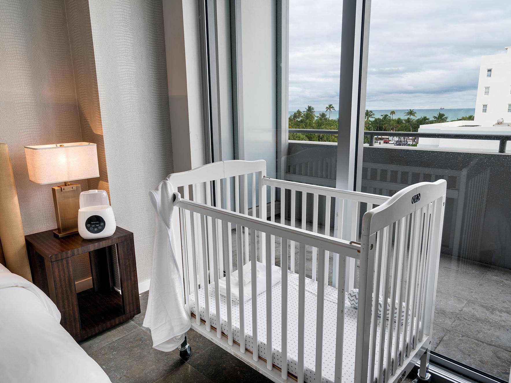 crib near bed in bedroom