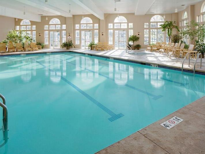 Indoor pool area with pool chairs at Westford Regency