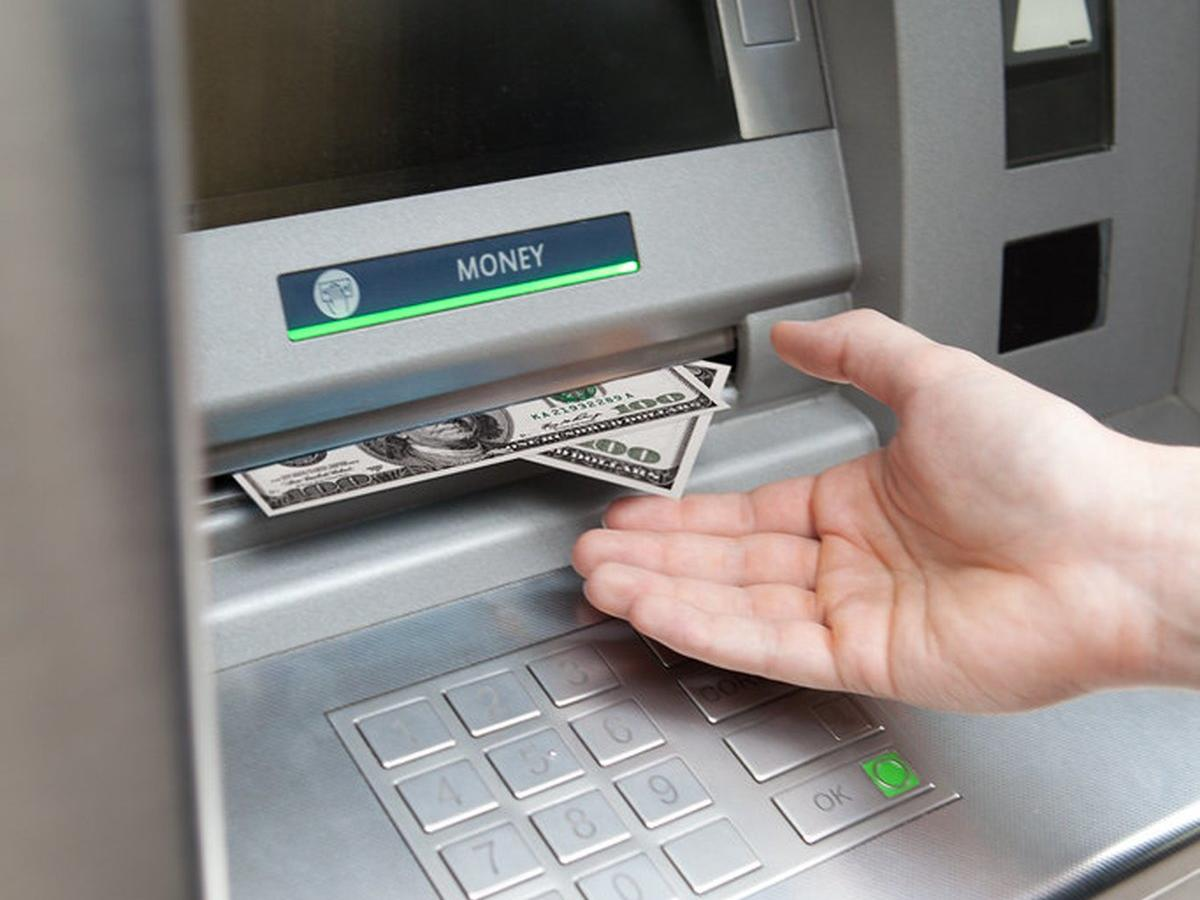 Hand withdrawing cash from ATM