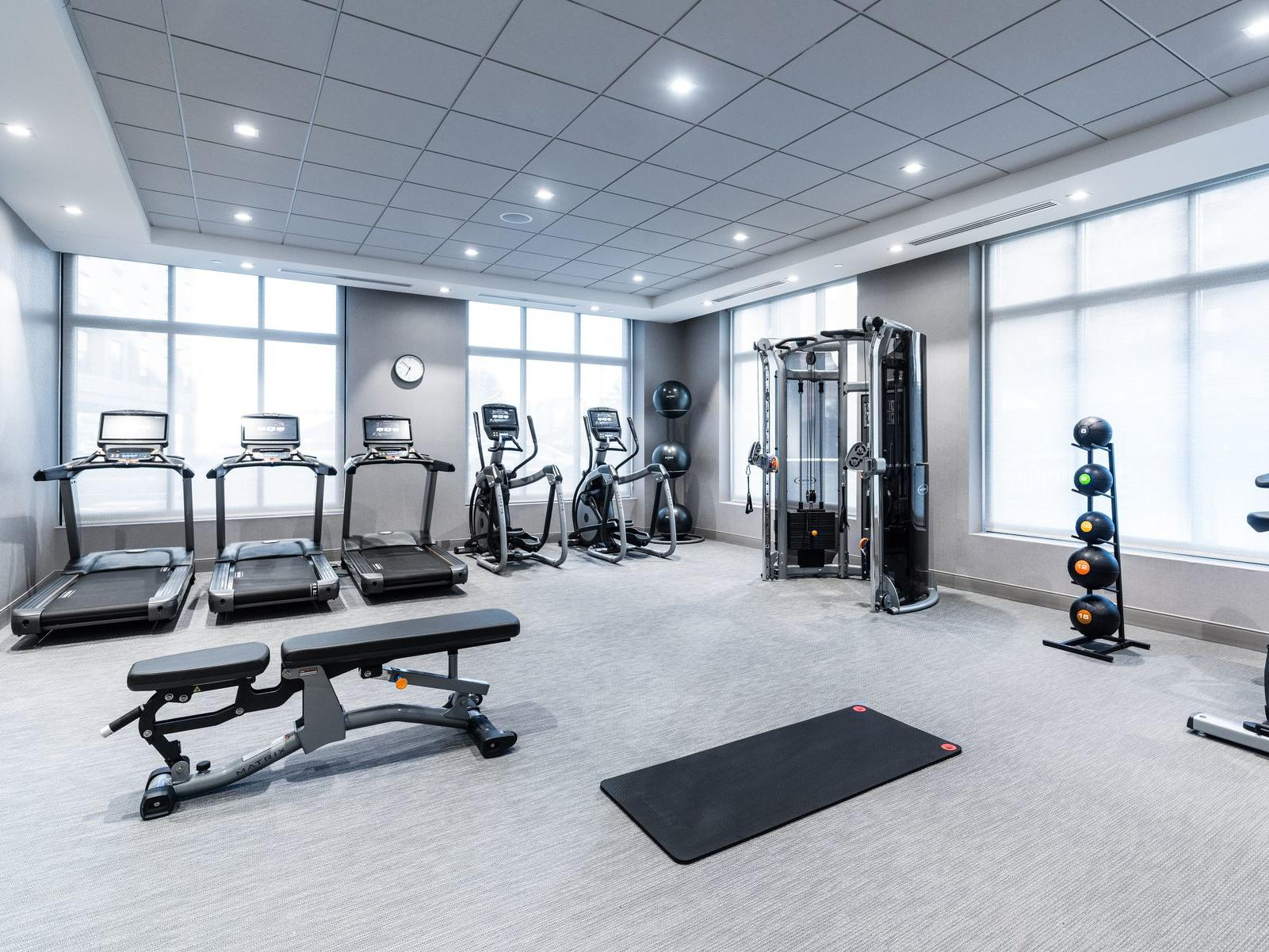 fitness center with treadmills, medicine balls and other workout equipment