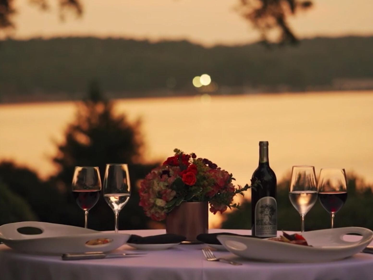 view of lake at sunset with wine, food, and flowers