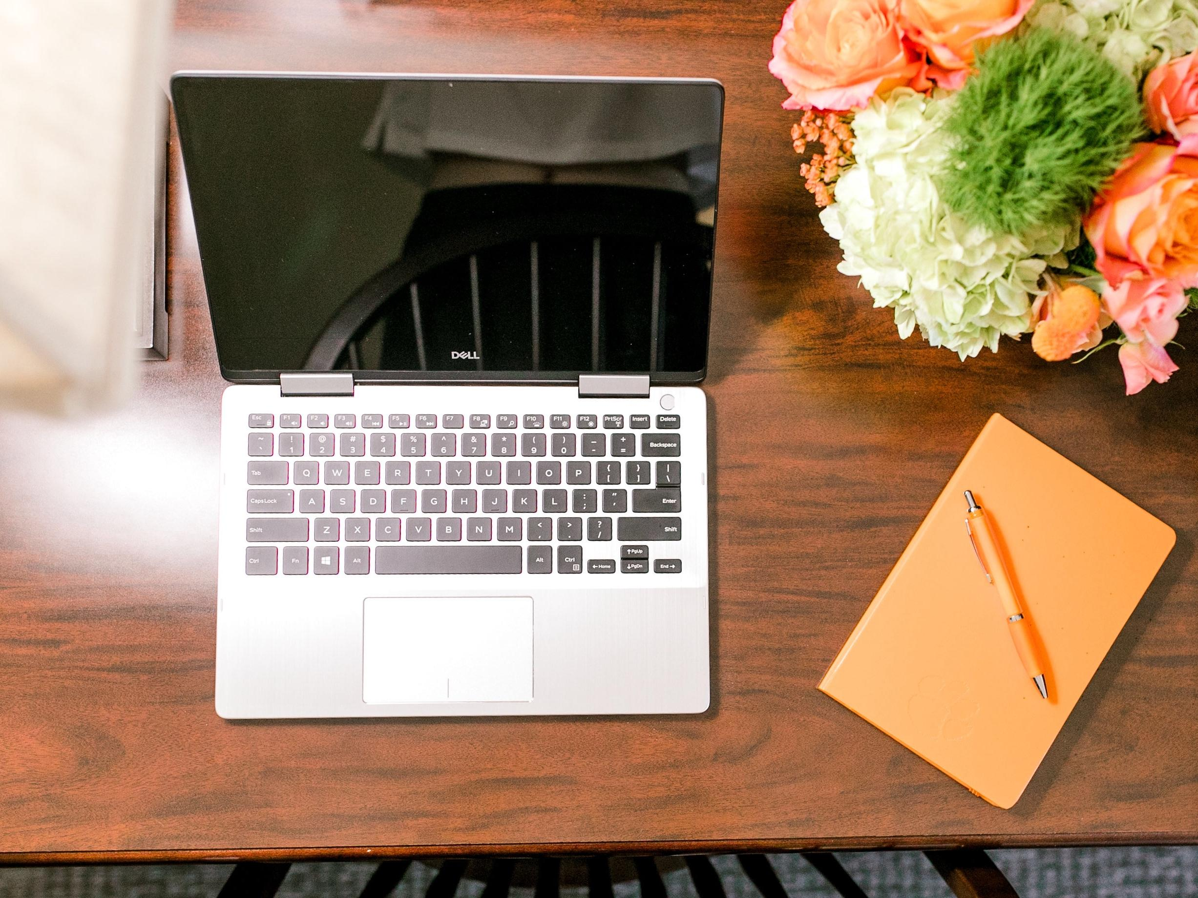 Laptop, notepad with pen, and flowers on tabletop