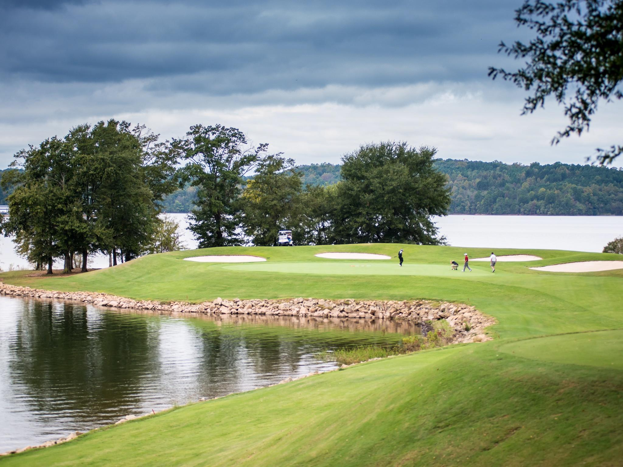 people playing on golf course hole with view of lake