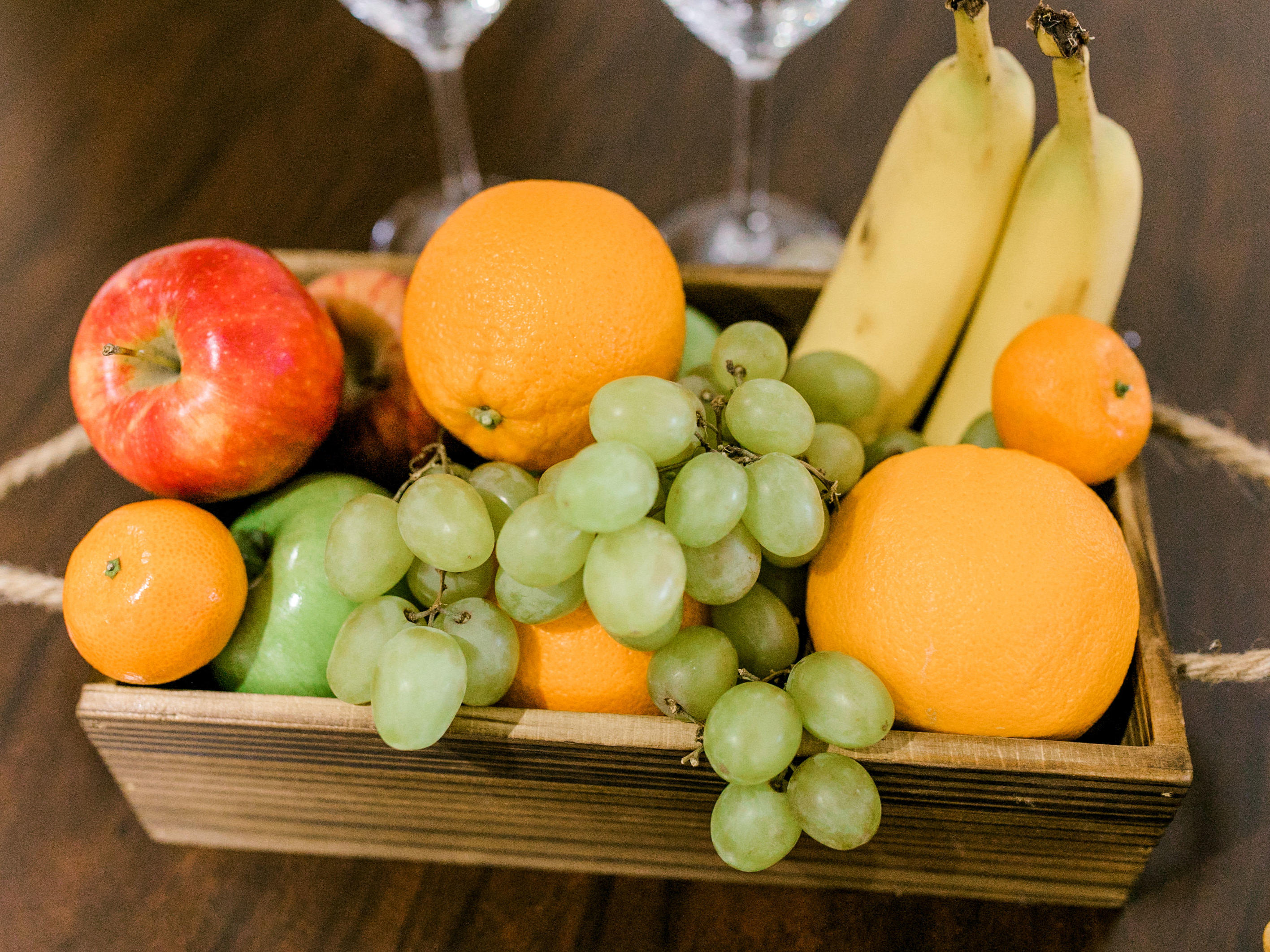 basket of fruit and wine glasses on table