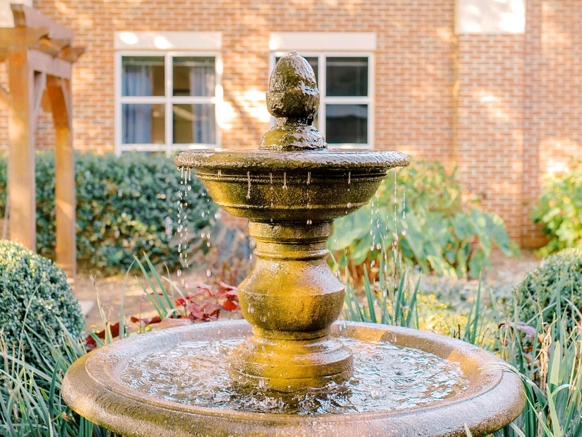 Fountain in patio area with landscaped area surrounding