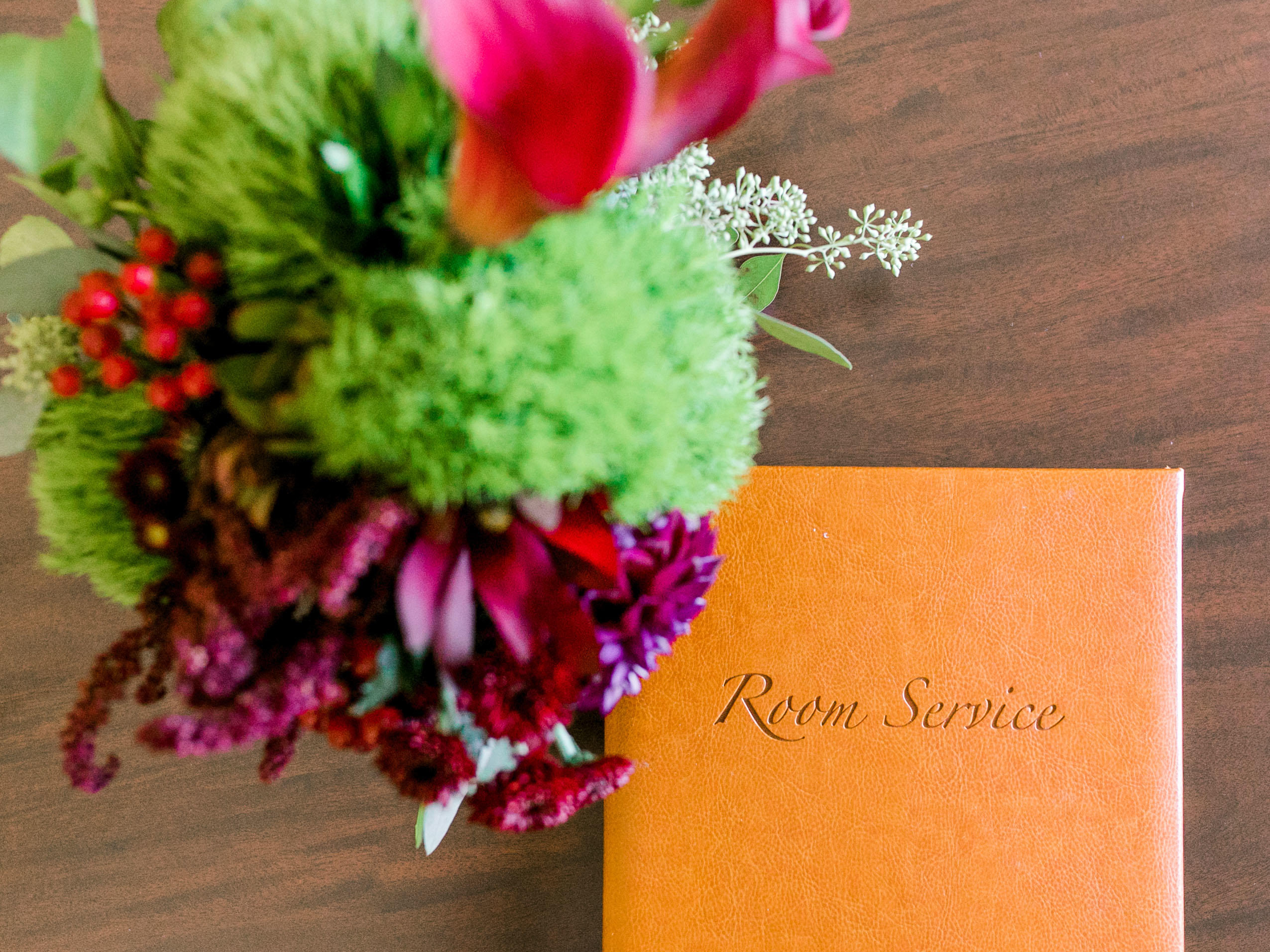 Room Service menu and flowers on table