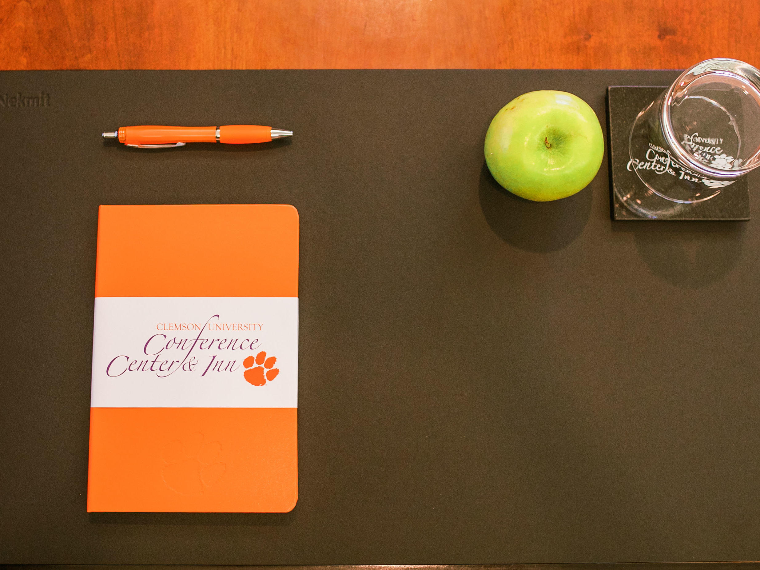 Notebook with pen, apple, coaster with glass, on a pad on table top