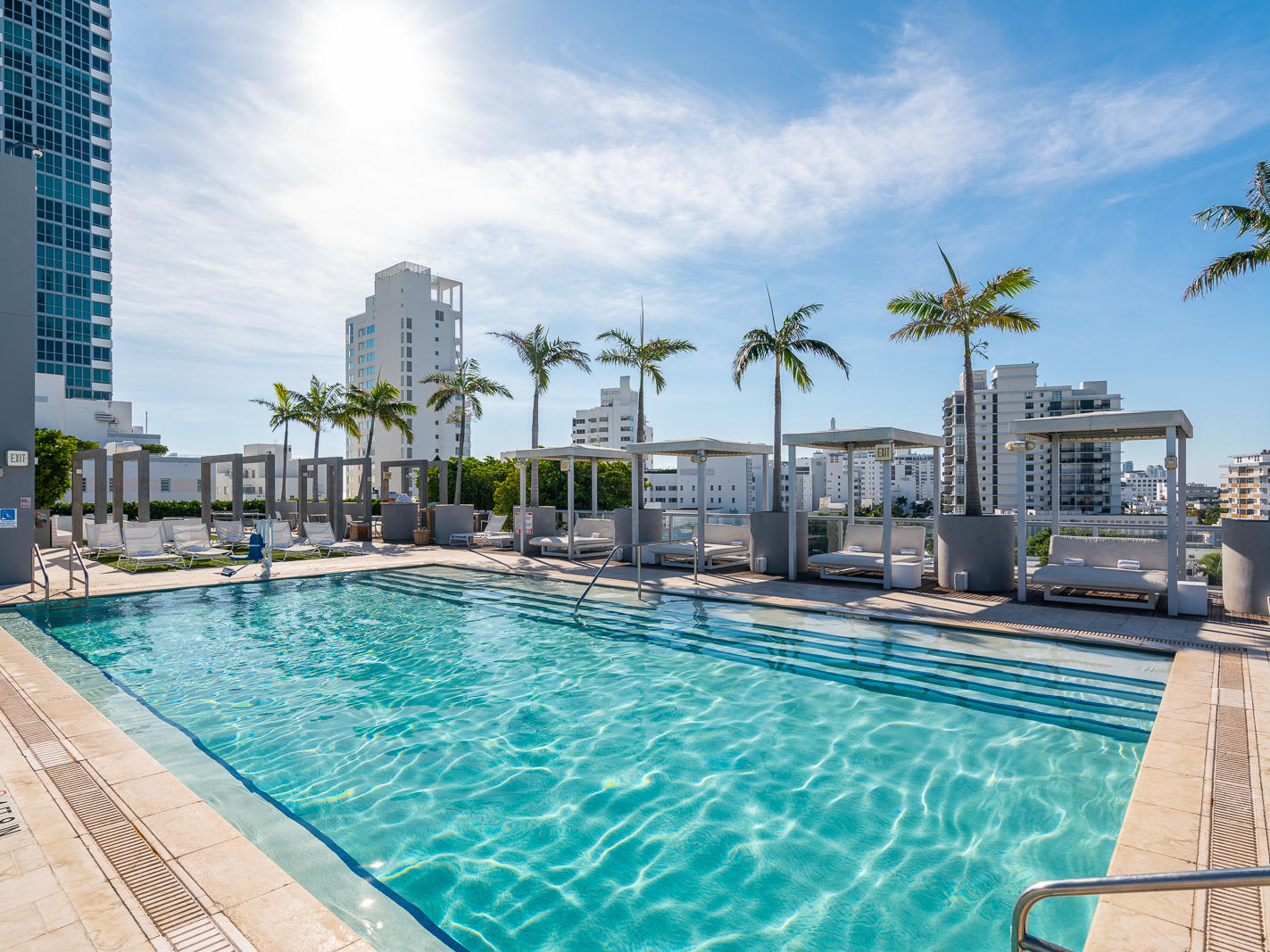rooftop pool with cabanas and palm trees