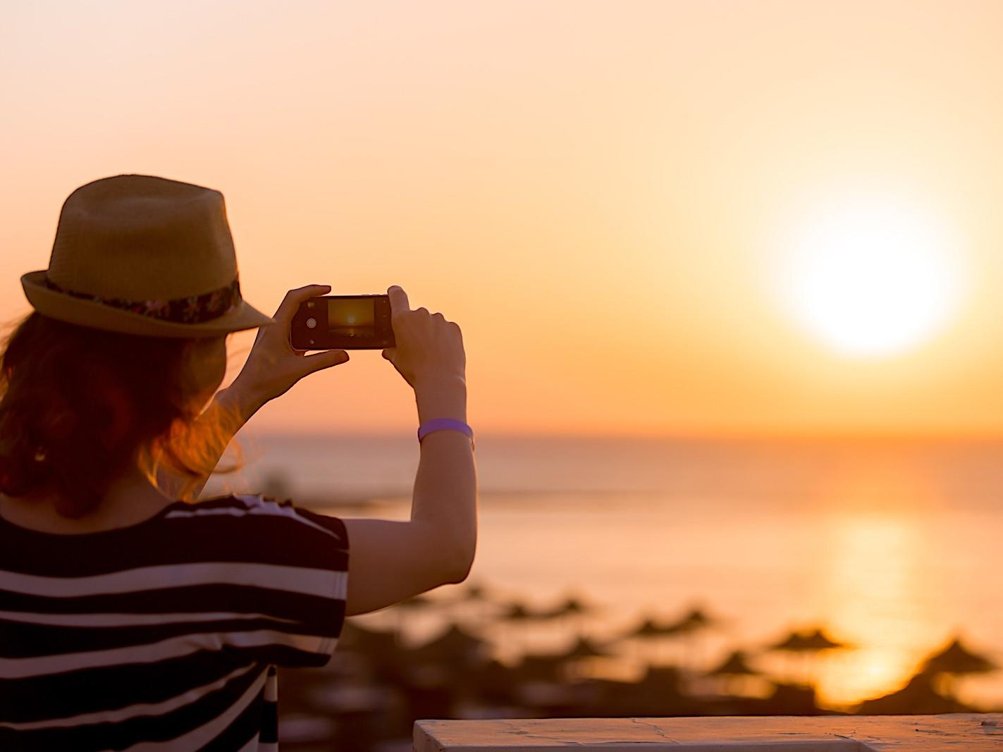 woman taking picture of the sunset