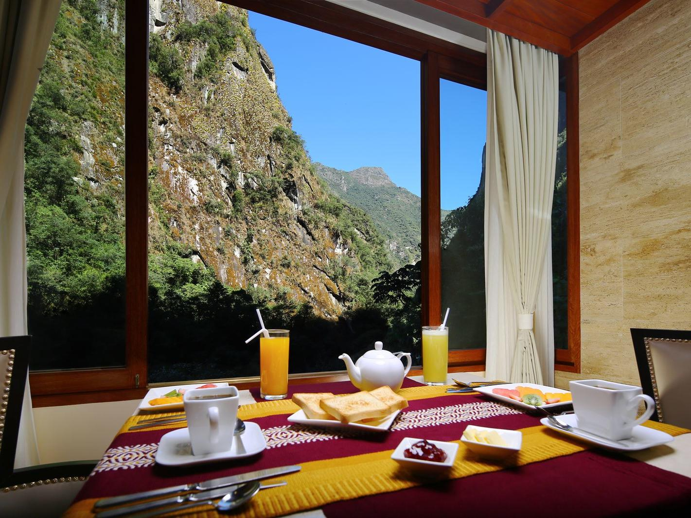 Breakfast table arranged with the mountain view at Hotel Sumaq