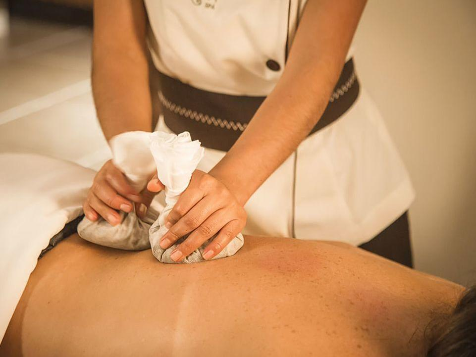 A masseuse treating a client in Aqlla Spa at Hotel Sumaq