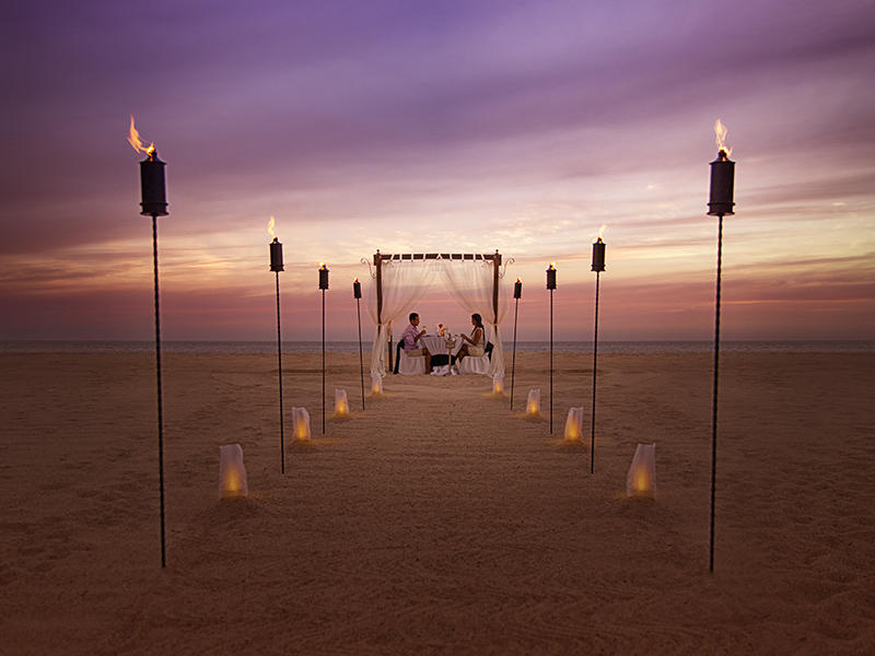 a walkway leading to two people eating on the beach