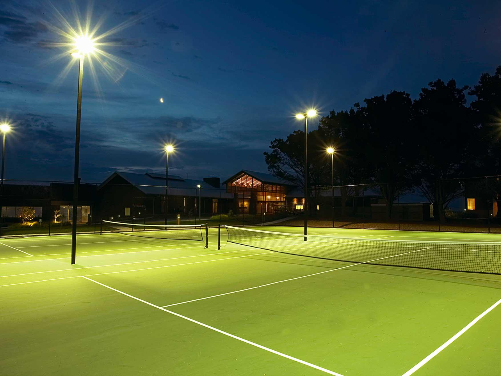 Lit tennis courts at night with lights on at Silverwater Resort