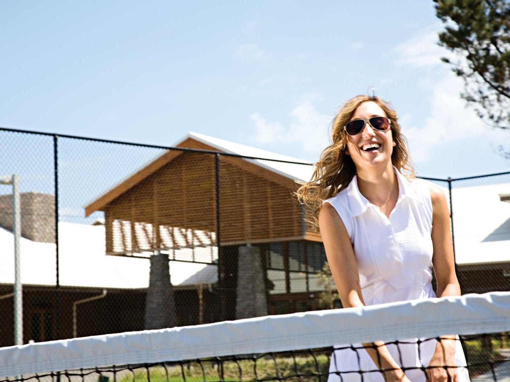 Woman near tennis net in Lit tennis court at Silverwater Resort