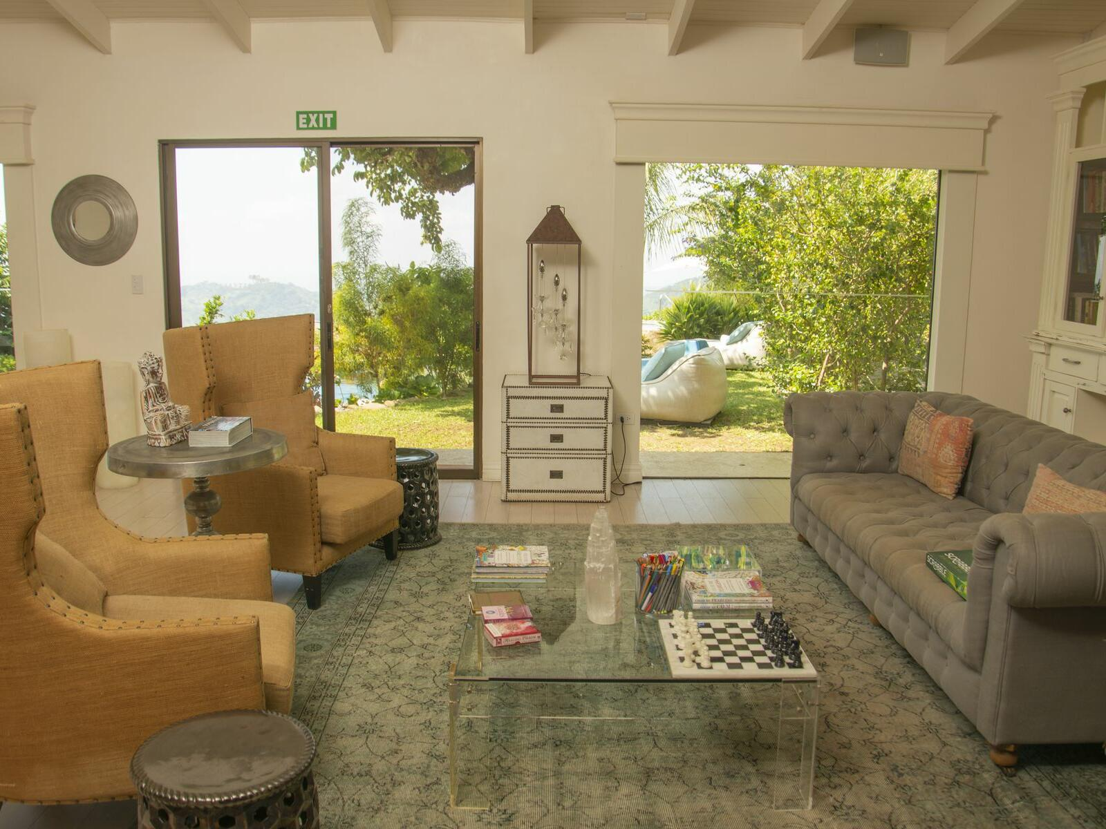 hotel living room with sofa, accent chair and balcony