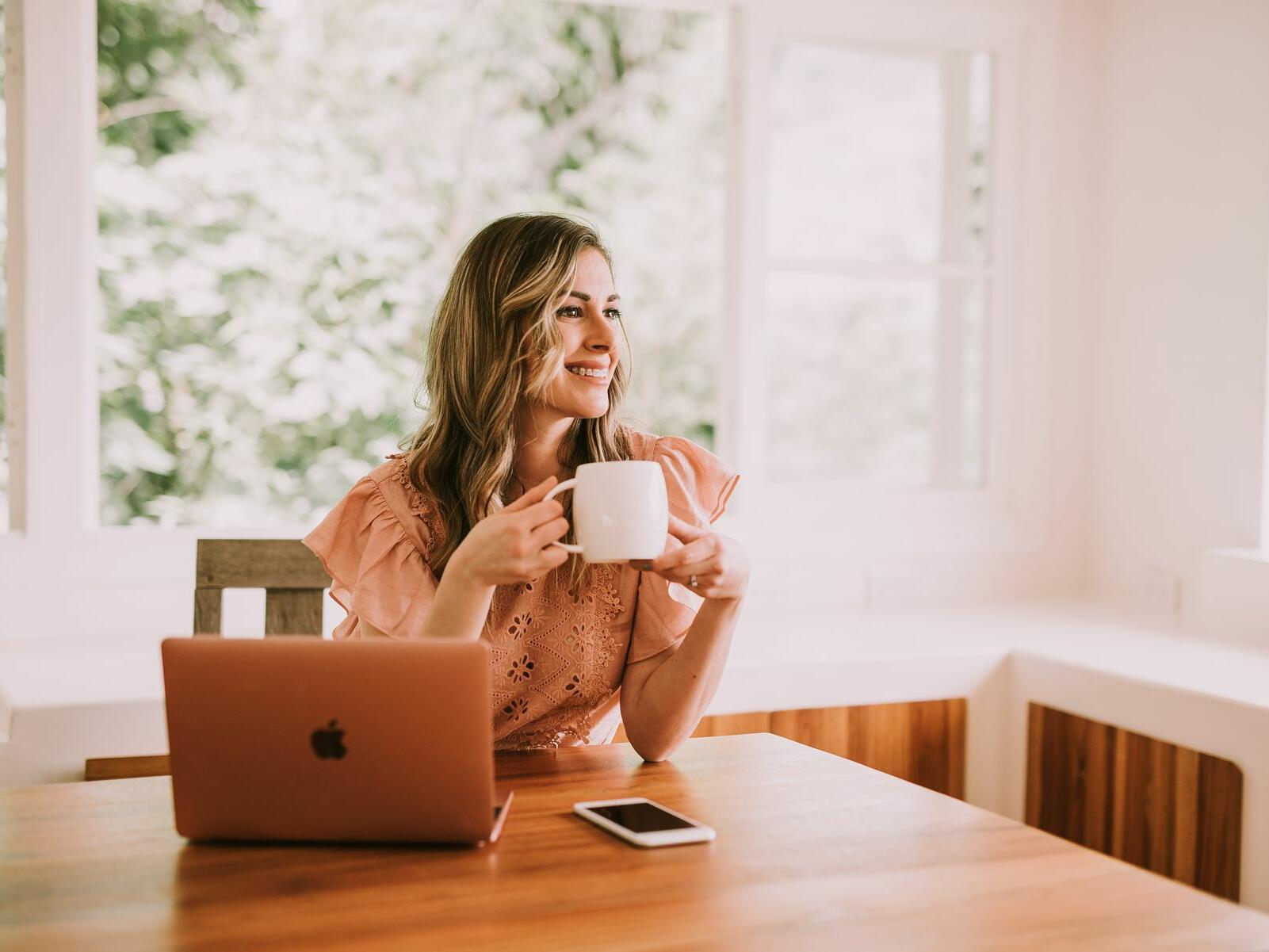woman sitting at desk with coffee and computer