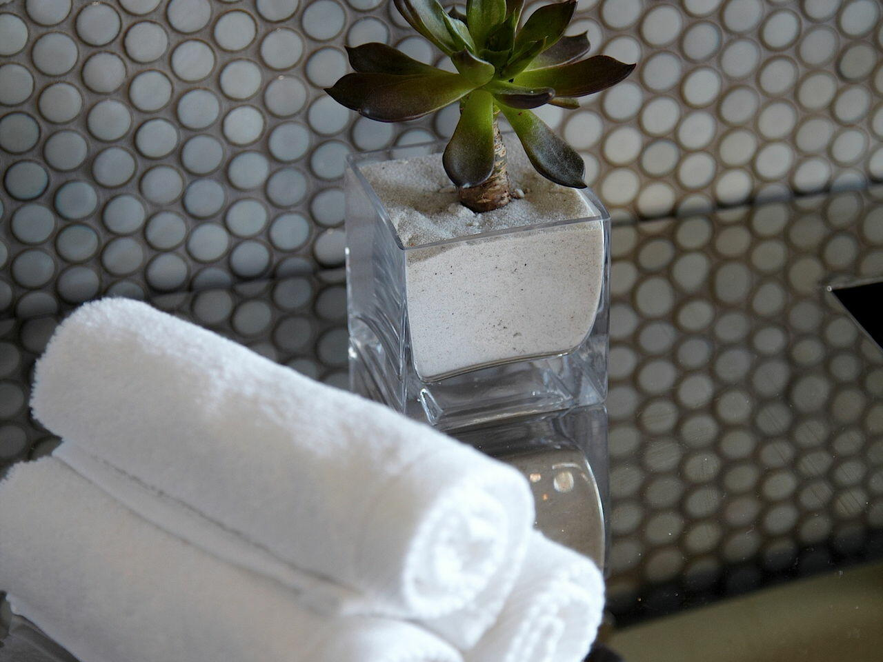 3 White towels on a table next to a plant at Dream Downtown NYC