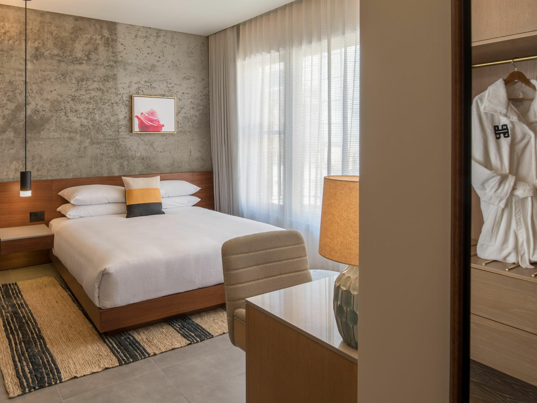 Hi-Lo hotel room with bed and robe in closet