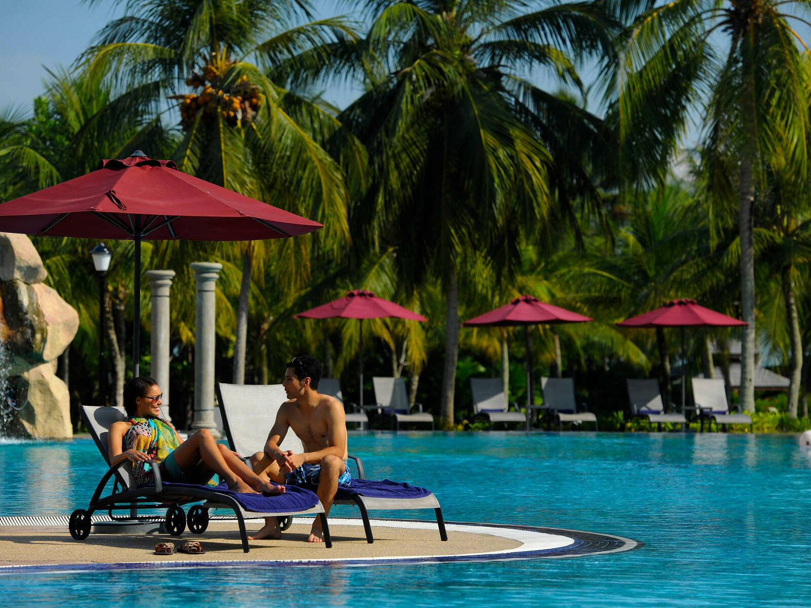 A couple on two pool chairs by the pool