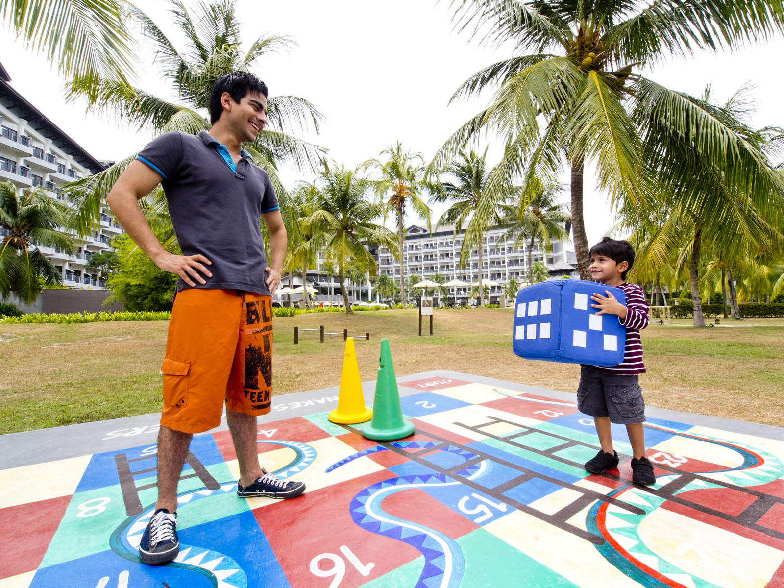 A man and a kid playing life size snake and ladders