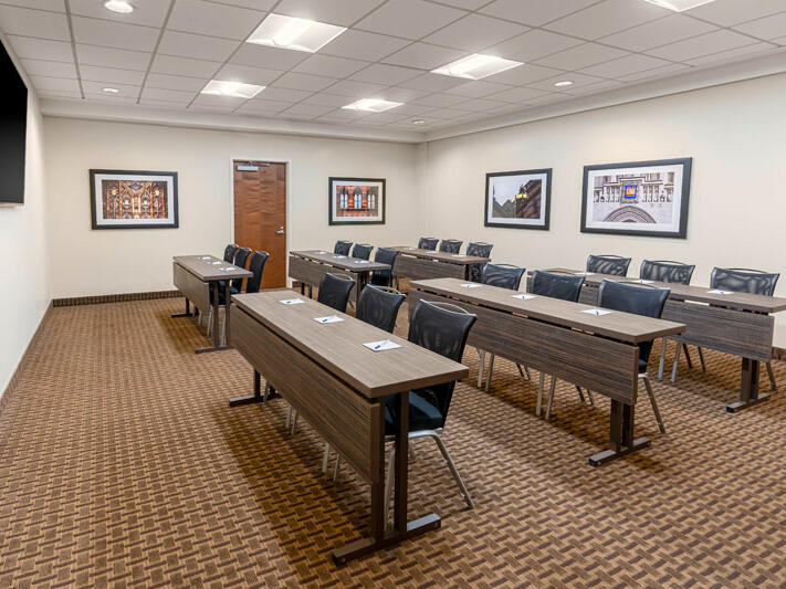 Meeting room with table and chairs set in classroom style with TV monitor.