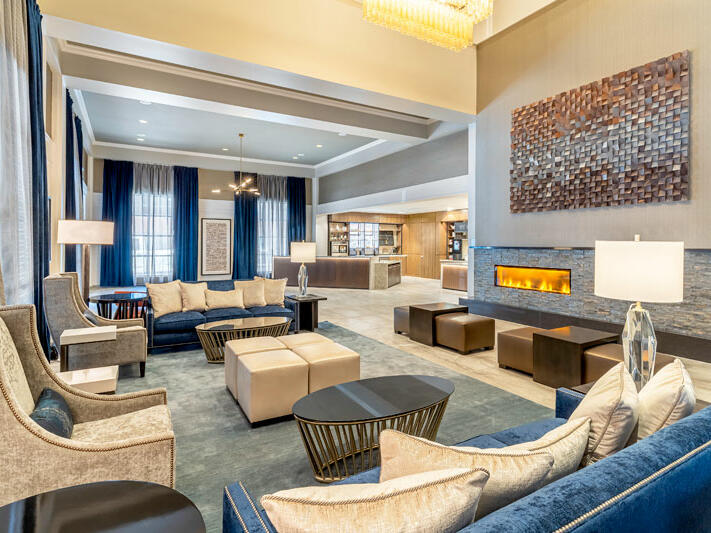 Lobby area with couches, chairs, table and fireplace.