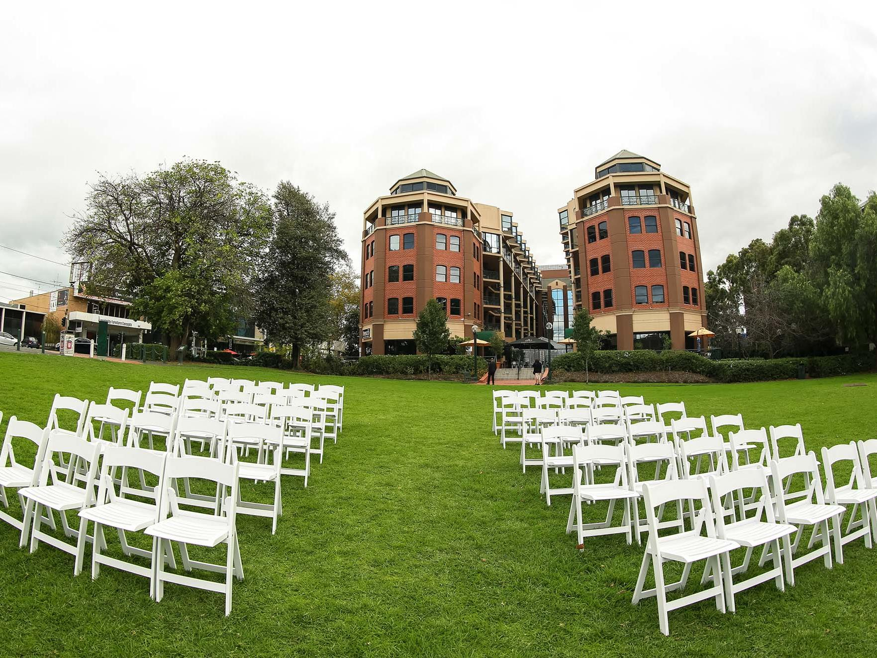 Amora Hotel Riverwalk Melbourne's Outdoor Wedding Venue with White Chairs Set Up