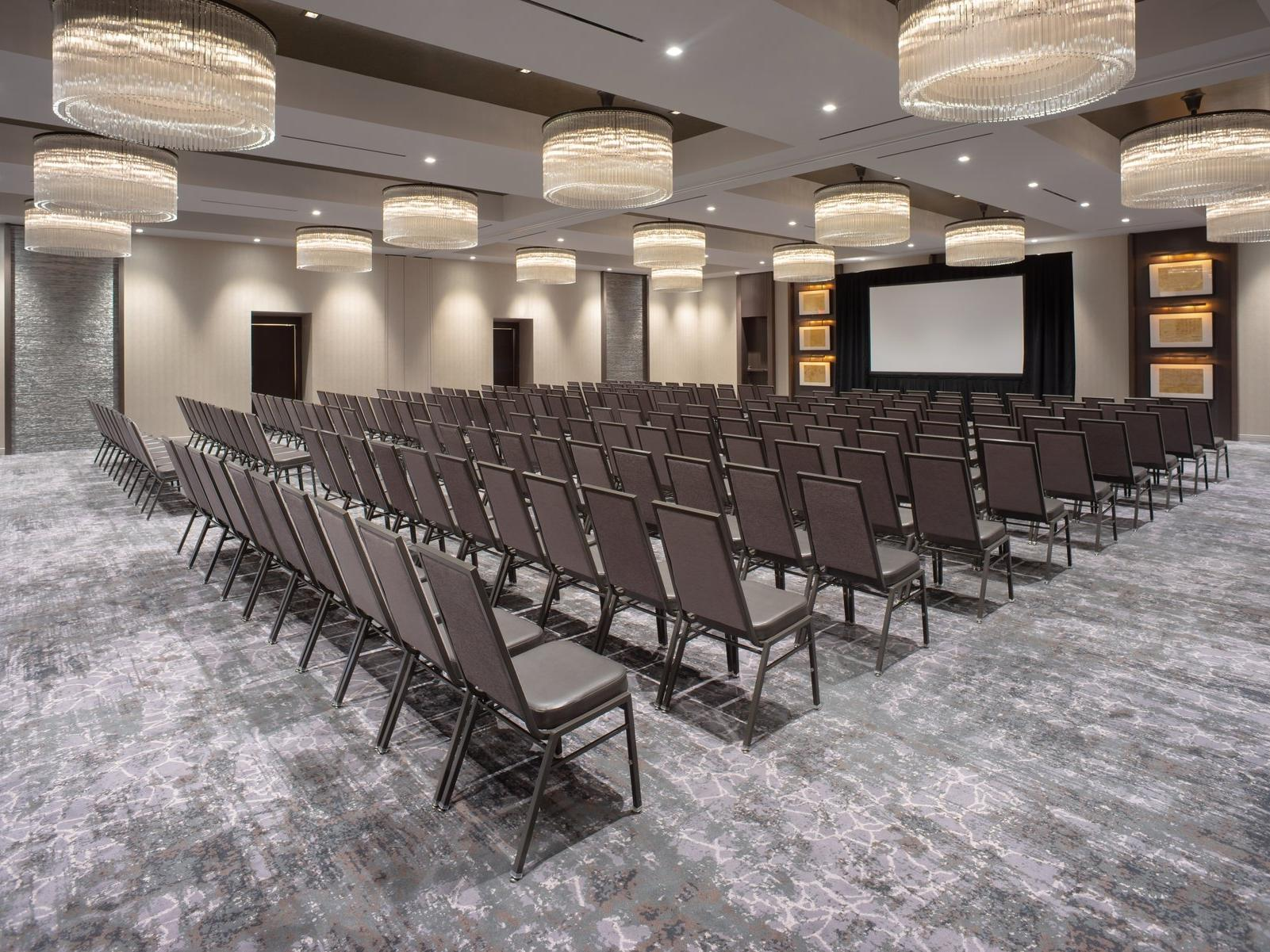 Meeting space set theater style with projector screen in front of room
