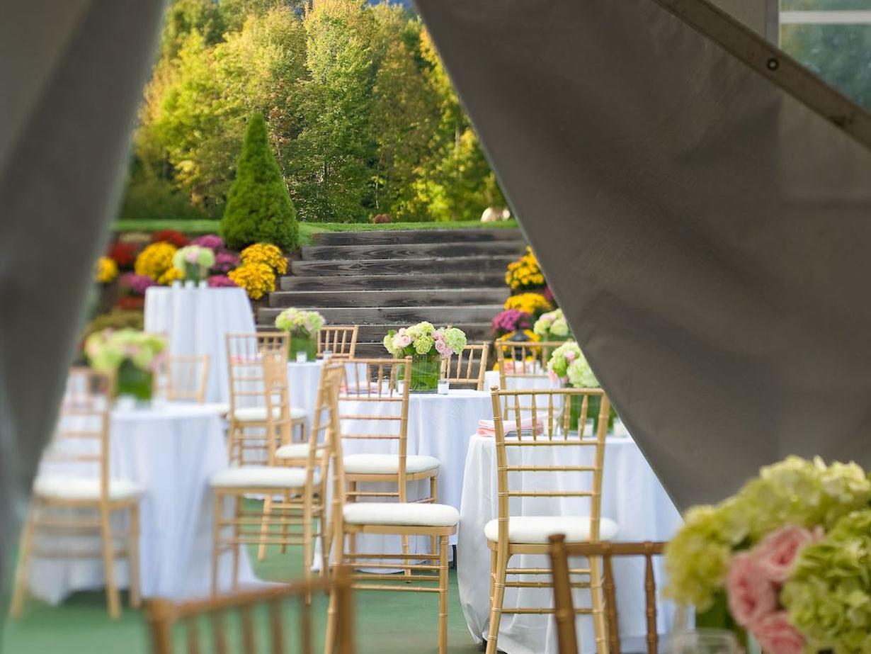 View of wedding reception tables within a pavilion tent.