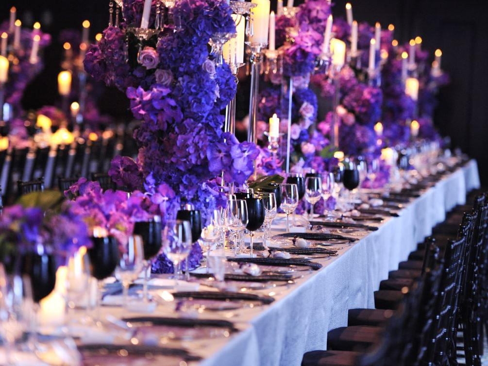 Long banquet table set for event with hydrangea and candle center pieces