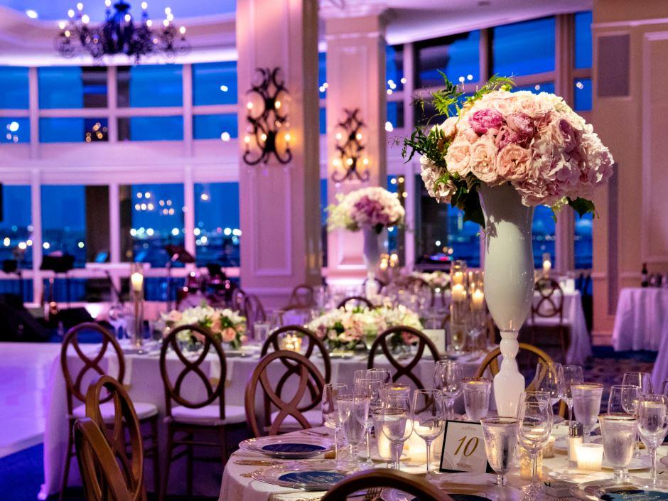 Event space set for wedding reception with tall floral center pieces