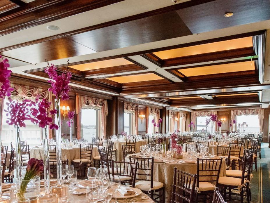 Banquet room set for event with tall floral center pieces