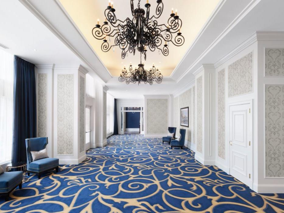 Event space hallway with chandeliers and wing back chairs by window