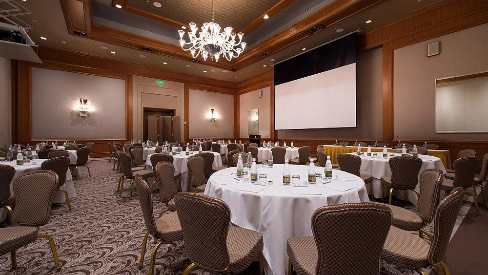 ballroom with chairs and white round tables