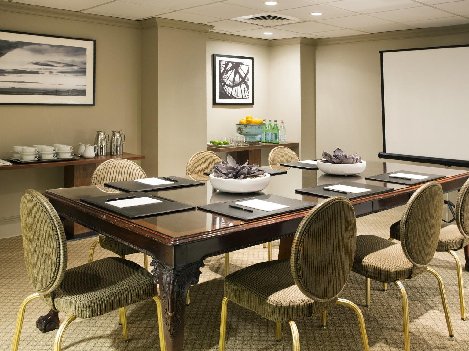 Meeting room with light colored walls and table set for 7